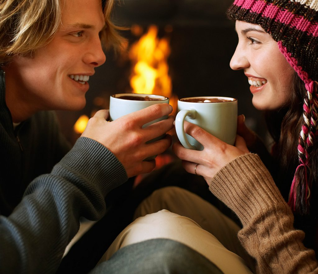 couple drinking hot chocolate by fireplace